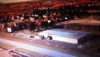 Vue aérienne de l'aréna en 1980, qui s'appelle maintenant l'aréna Madeleine Auclair en mémoire de cette dame qui a été longtemps échevin à Farnham. Sur cette photo, on peut voir que la 104 est toute neuve, il y a rien sur les cotés.